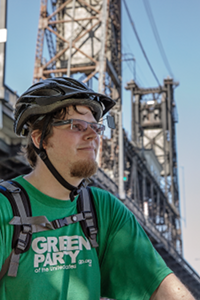 Seth with bicycle helmet on, steel bridge in background